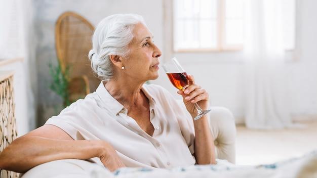 Une femme âgée assise sur un canapé tenant un verre d'alcool rêverie