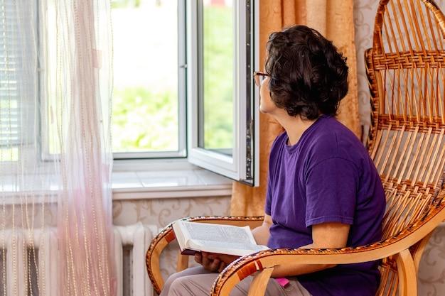 Une femme âgée assise sur une chaise tenant une bible et regardant par la fenêtre, méditant après avoir lu la bible