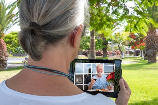 Une femme âgée assise dans un pré lors d'un appel vidéo via la tablette avec un membre de la famille