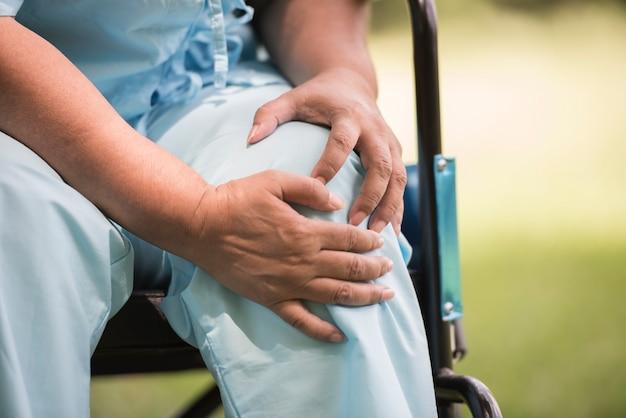 Femme âgée assise sur un fauteuil roulant avec une douleur au genou