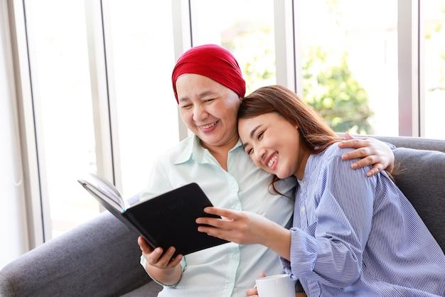 Une femme âgée atteinte d'un cancer portant un foulard se détend à la maison avec sa fille adulte et lisant un livre en souriant. les femmes sont pleines d'espoir pour l'avenir.