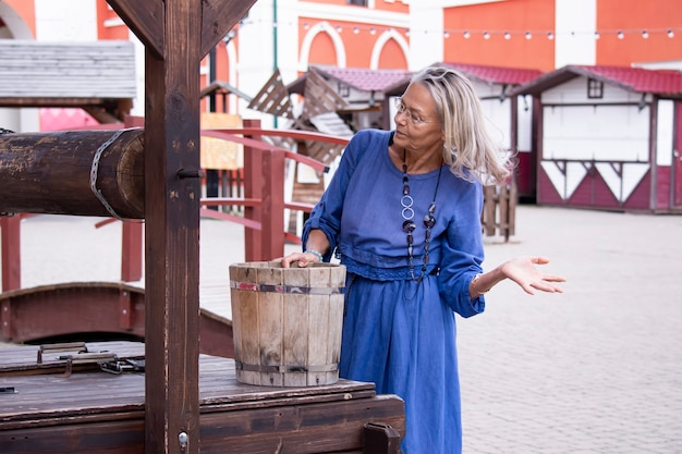 Une femme âgée attirante se tient près d'un vieux puits tenant un seau en bois et réfléchit à la façon de verser de l'eau
