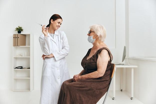 Femme âgée au rendez-vous des médecins plaisir d'injection de main