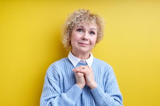Femme âgée aux cheveux gris gardant les mains ensemble à l'avant, à la recherche amicale et agréable