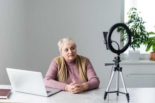 Femme âgée ayant un appel vidéo avec sa famille, souriant et agitant. heure de quarantaine.