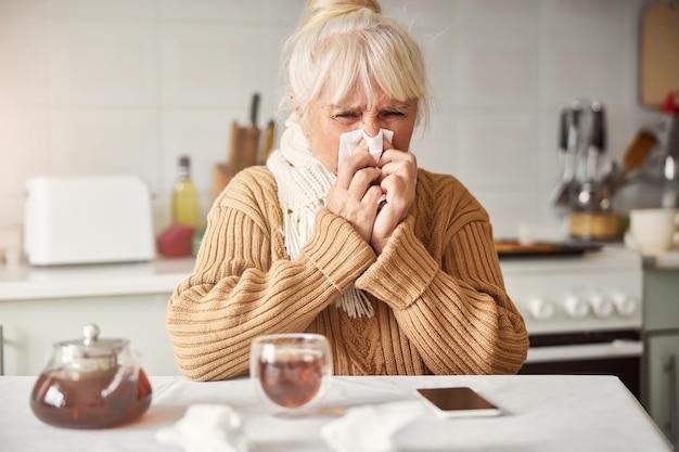 Femme âgée ayant le nez qui coule et ne se sentant pas bien