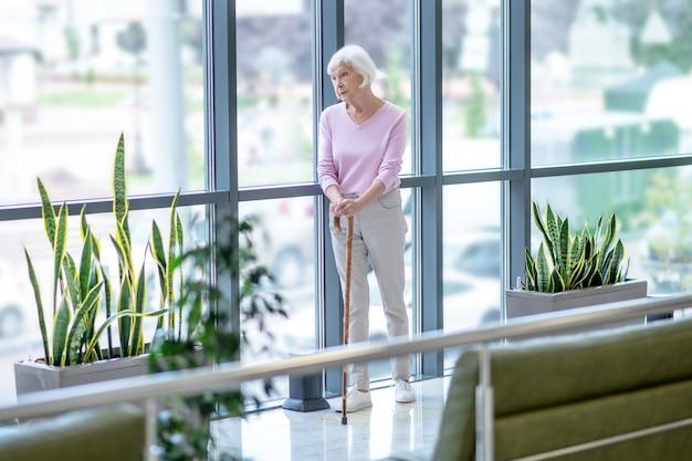 Femme âgée avec un bâton de marche debout près de la fenêtre
