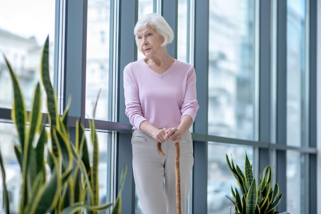 Femme âgée avec un bâton de marche debout et à la réflexion