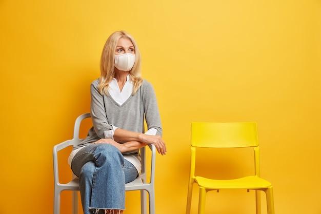 Une femme âgée blonde a une expression réfléchie concentrée à distance porte un masque de protection pendant l'épidémie de coronavirus reste seule à la maison pose sur une chaise au-dessus d'un mur jaune.