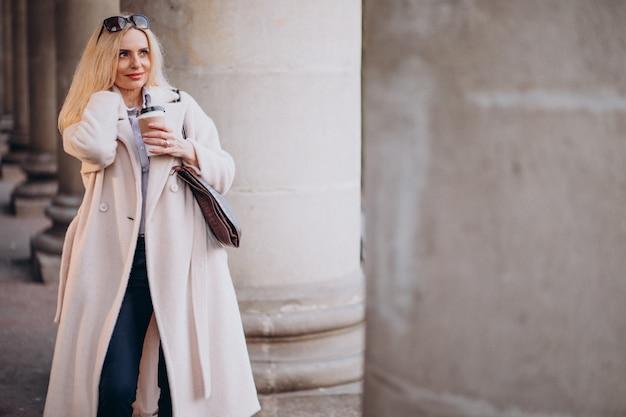 Femme âgée, boire café, dehors, rue