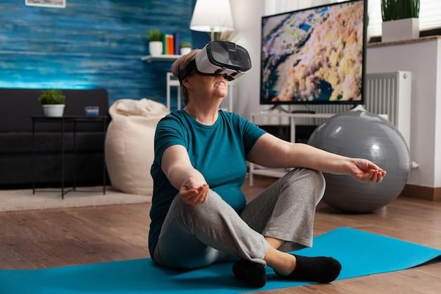 Femme âgée en bonne santé utilisant un casque de réalité virtuelle méditant en position de lotus sur un tapis de yoga dans le salon pendant l'entraînement de méditation