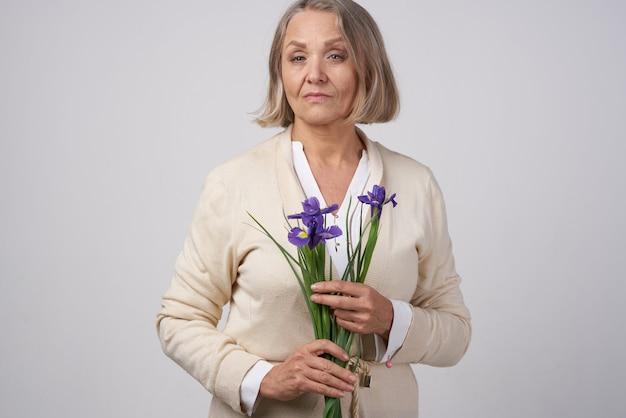 Femme âgée avec un bouquet de fleurs cadeau anniversaire attentionné
