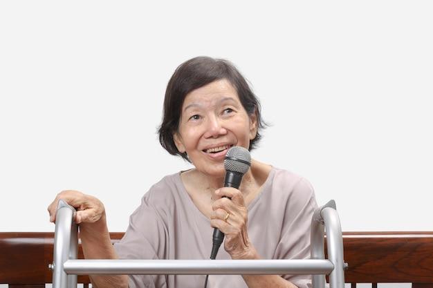 Une femme âgée chante une chanson au microphone à la maison.