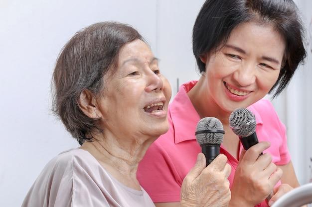 Une femme âgée chante une chanson avec sa fille à la maison.