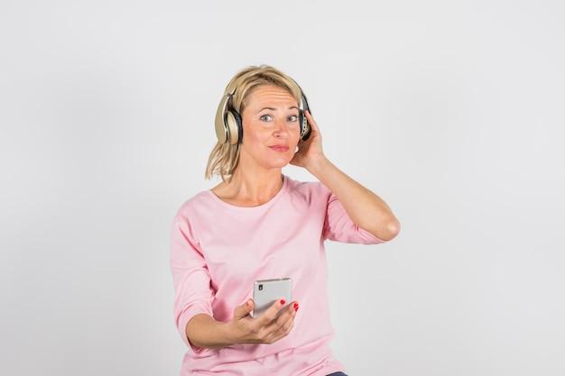 Femme âgée en chemisier rose avec un casque à l'aide de smartphone