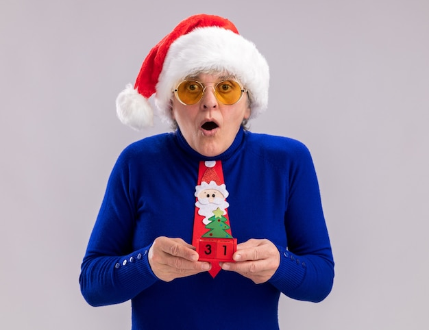 Femme âgée choquée dans des lunettes de soleil avec bonnet de noel et cravate de père noël tenant ornement d'arbre de noël
