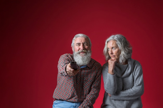 Une femme âgée en colère regarde son mari changer de chaîne avec une télécommande