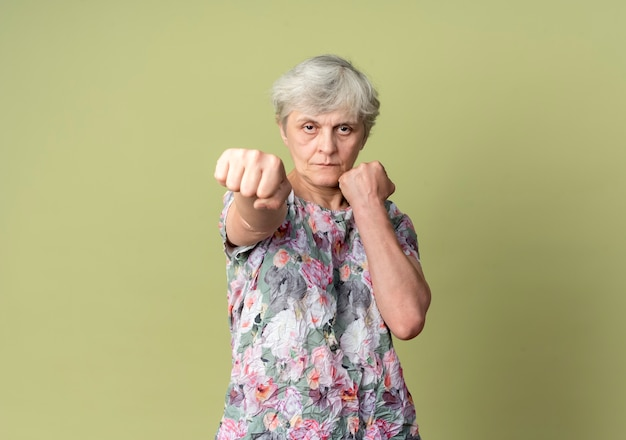 Femme âgée confiante garde les poings prêts à poinçonner isolé sur mur vert olive