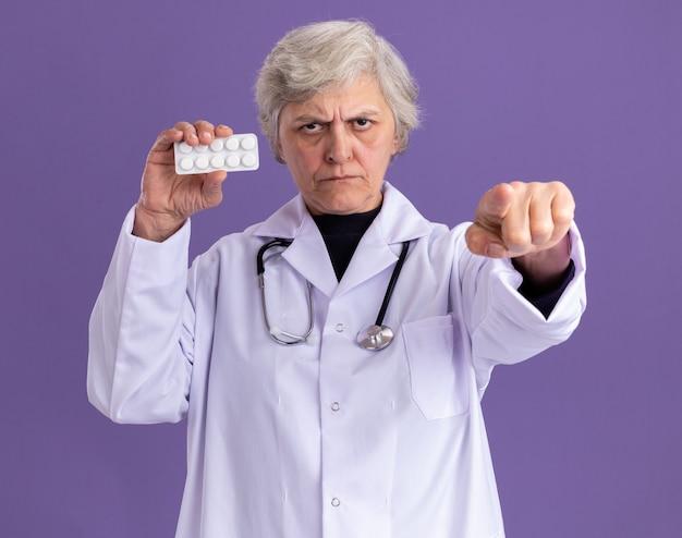 Femme âgée confiante en uniforme de médecin avec stéthoscope tenant l'emballage de la pilule et pointant vers l'avant