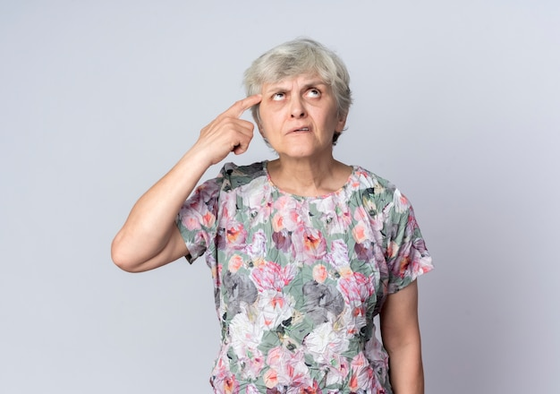 Femme âgée confuse met le doigt sur le temple en levant isolé sur mur blanc