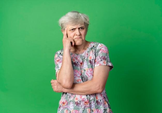 Femme âgée confuse met la main sur le menton à côté isolé sur mur vert