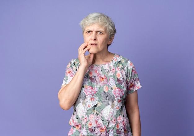 Femme âgée confuse met la main sur le menton isolé sur mur violet