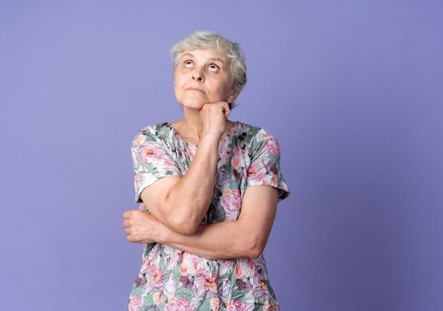 Femme âgée confuse met la main sur le menton en levant isolé sur mur violet