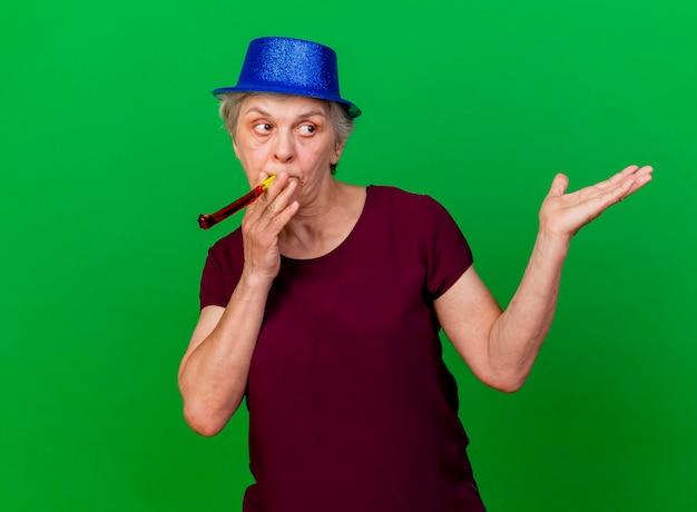 Femme âgée confuse portant chapeau de fête soufflant sifflet et tenant la main ouverte sur le vert