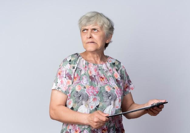 Femme âgée confuse tient le presse-papiers à la recherche d'isolement sur le mur blanc