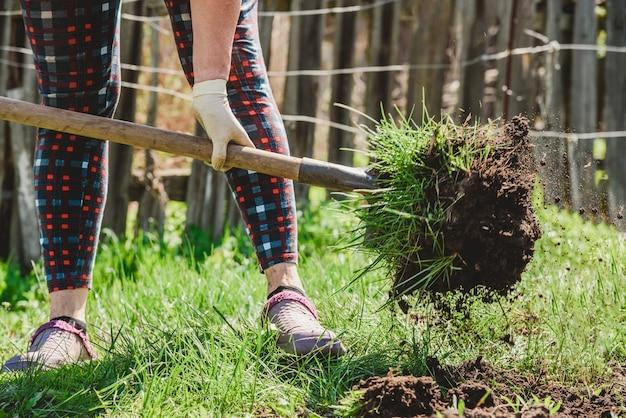 Une femme âgée creuse la terre avec une pelle dans son jardin du village