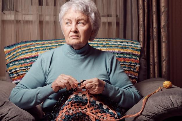 Femme âgée, crochet sur chaise à la maison, loisirs créatifs.