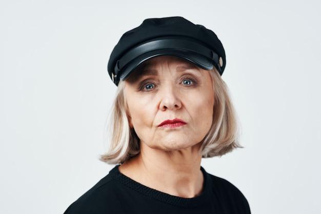 Femme âgée dans un fond clair de gros plan de mode de chapeau noir