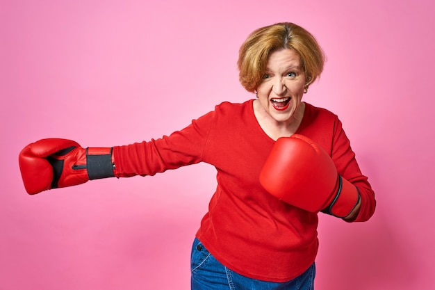 Femme âgée dans des gants de boxe. le concept de la lutte contre la vieillesse.