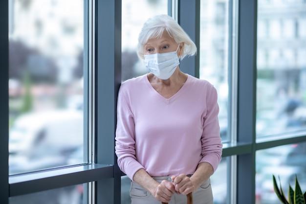 Femme âgée dans un masque facial debout près de la fenêtre