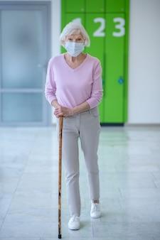 Femme âgée dans un masque facial marchant dans le couloir