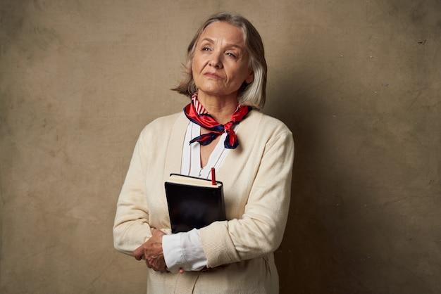 Femme âgée dans une robe de chambre avec un cahier dans ses mains travail en studio