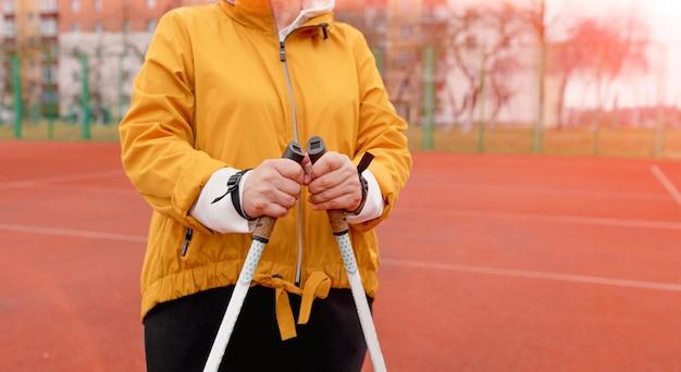 Une femme âgée dans une veste de sport jaune pratique la marche nordique à l'extérieur sur le tapis roulant en caoutchouc des stades.