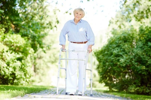 Une femme âgée avec déambulateur au parc