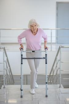 Femme âgée avec un déambulateur dans les escaliers