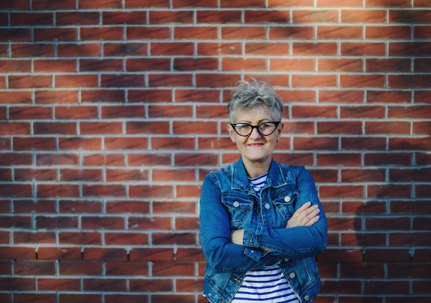 Femme âgée debout à l'extérieur sur fond de mur de briques, regardant la caméra.