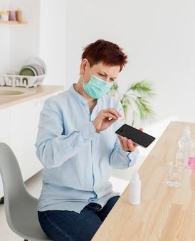 Femme âgée désinfectant son smartphone tout en portant un masque médical