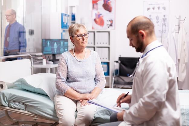 Femme âgée à l'écoute d'un médecin parlant du traitement en salle d'examen