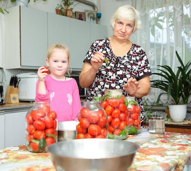 Une femme âgée et un enfant dans la cuisine préparant des tomates en conserve