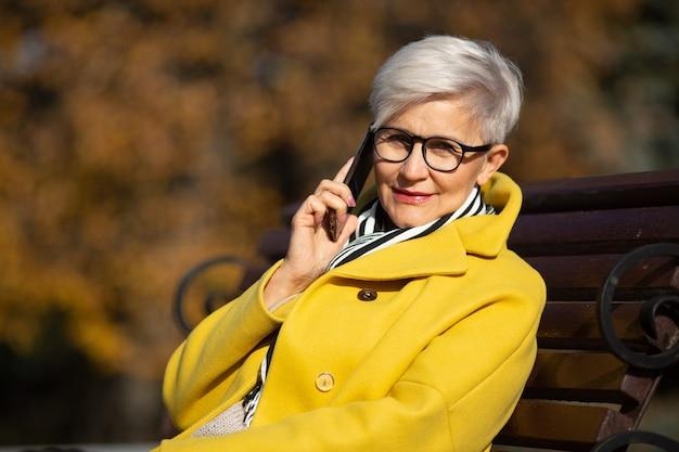 Femme âgée est assise sur un banc à parler au téléphone