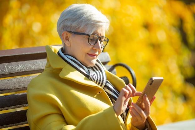 Femme âgée est assise sur un banc avec un téléphone