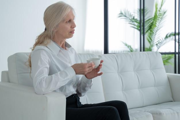 Une femme âgée est assise sur le canapé, boit du café ou du thé et regarde par la fenêtre