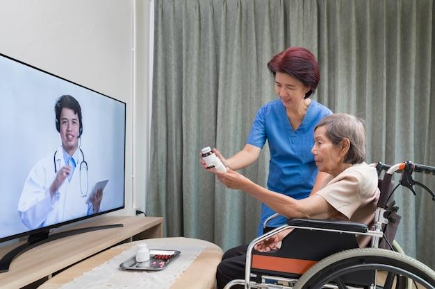 Une femme âgée est assise à la maison après avoir consulté un médecin en ligne.