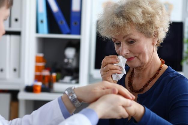 Une femme âgée est bouleversée lors d'un rendez-vous chez le médecin et essuie ses larmes avec une serviette.
