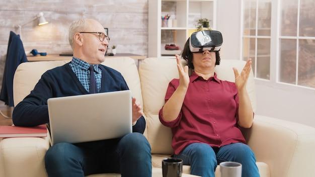Femme âgée étonnée tout en utilisant des lunettes de réalité virtuelle sur un canapé avec son mari à côté d'elle à l'aide d'un ordinateur portable.