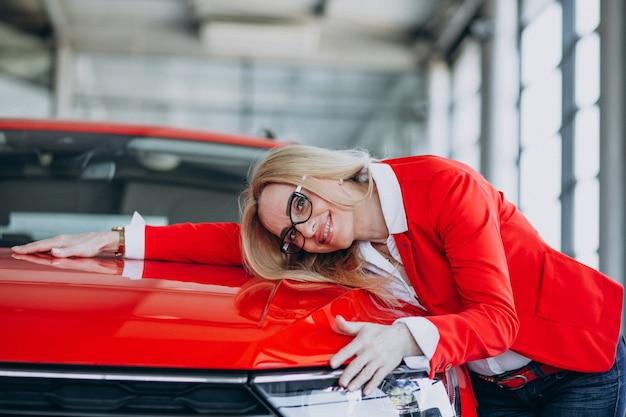 Femme âgée étreignant un mobile auto dans une salle d'exposition de voiture